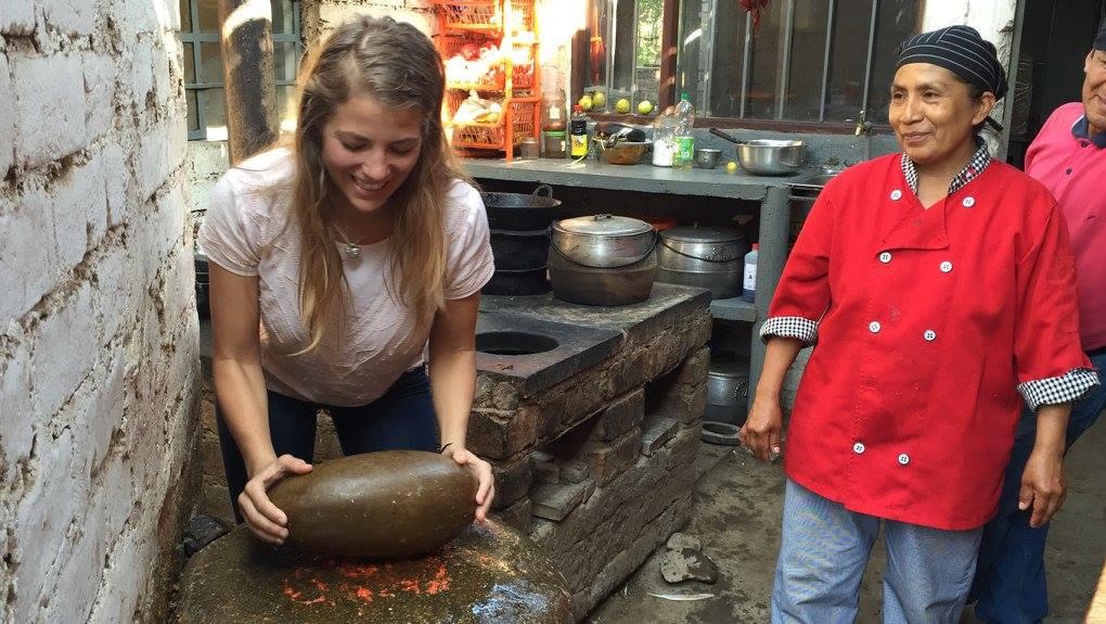 Peace Corps Volunteer making aji using the batan